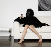 Young Woman dressed in Gorilla suit using mobile
