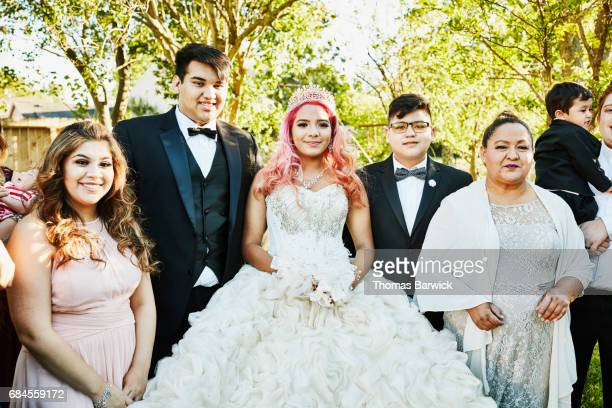 Young woman dressed in quinceanera gown standing in backyard surrounded by family