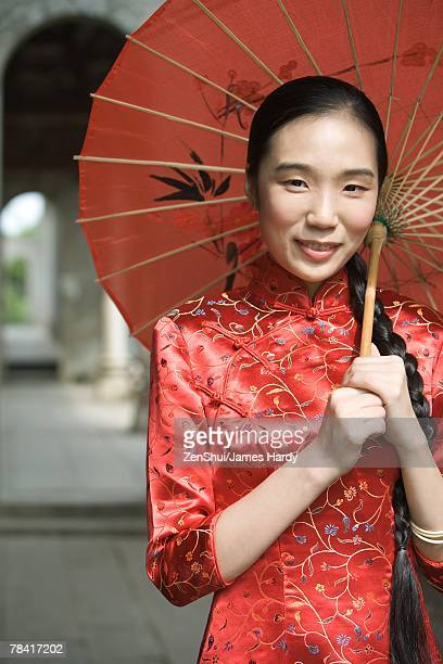 Young woman dressed in traditional Chinese clothing, standing under parasol, portrait