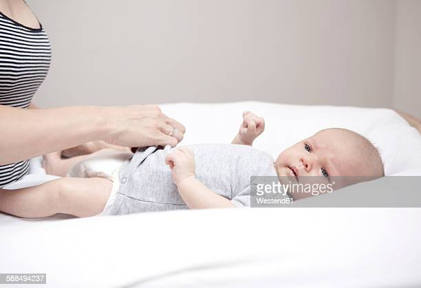 Young woman dressing baby lying on changing table