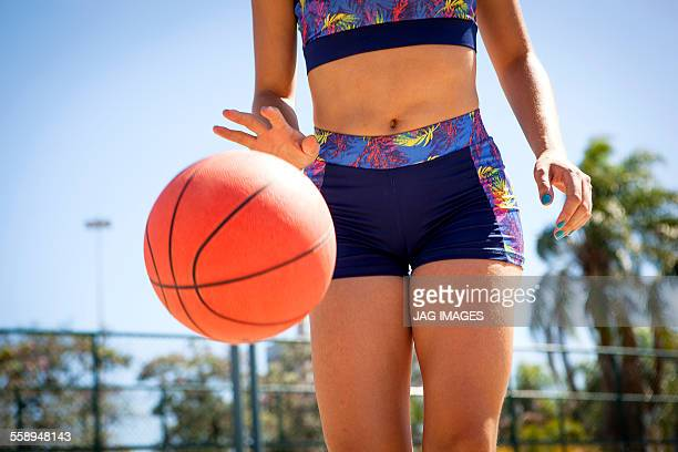Young woman dribbling basketball, mid section