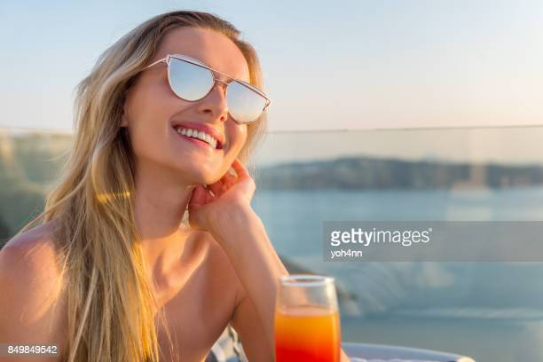 Young woman & drink on terrace