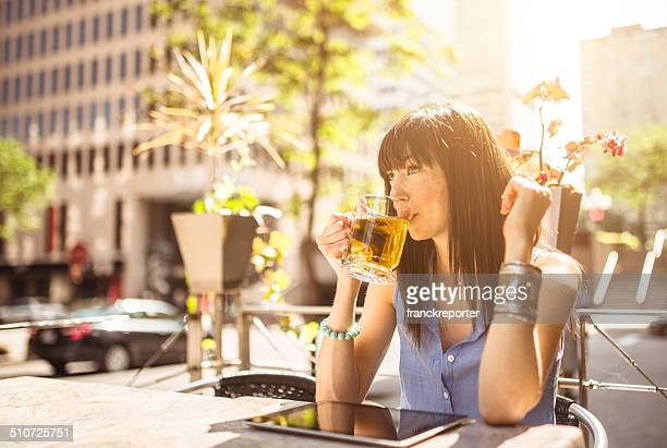 young woman drinking a tea on the city and surfing