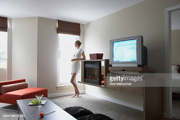 Young woman drinking alcoholic beverage beside window in hotel room