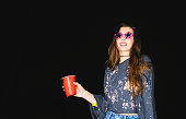 Hipster young woman having fun drinking and partying with funny sunglasses at night