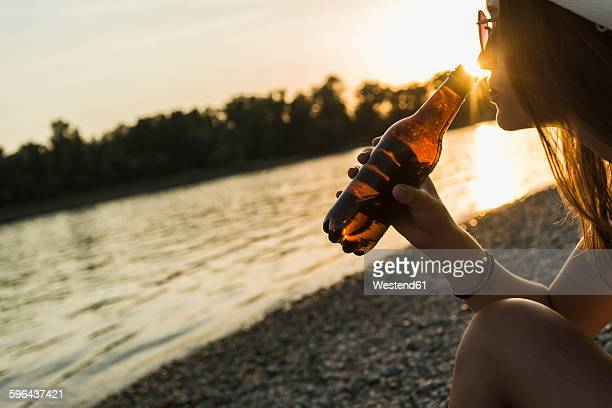 Young woman drinking beer at the riverside at sunset