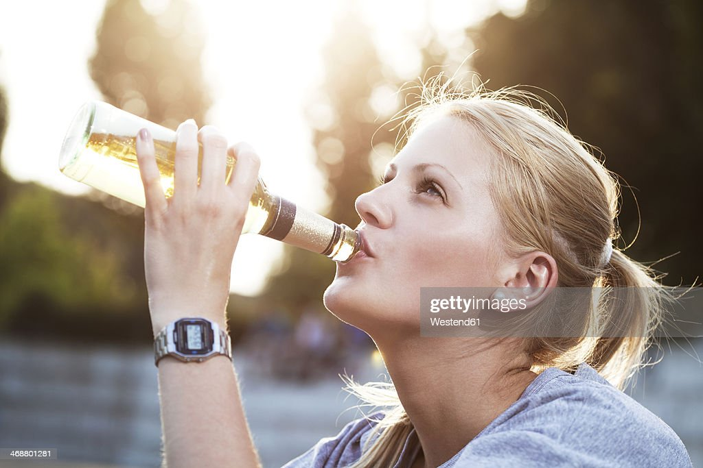 Young woman drinking beer of a bottle