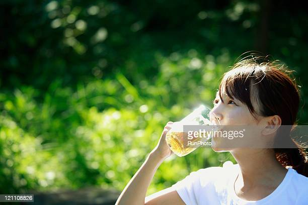 young woman drinking beer outside