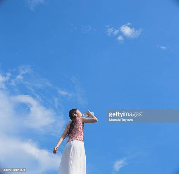 Young woman drinking bottled water under blue sky