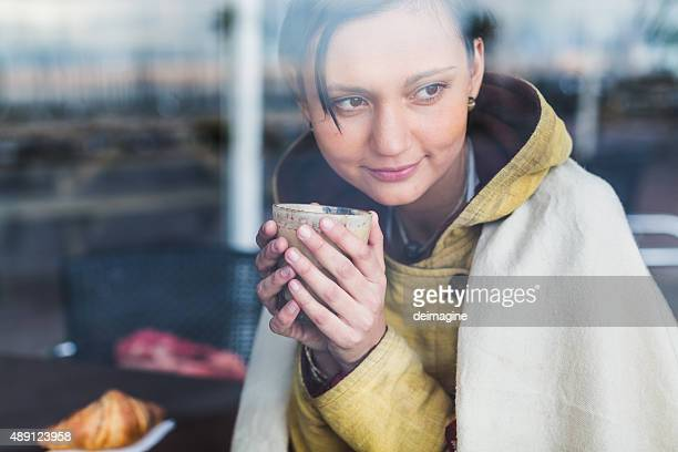 Young woman drinking capucino and looking out of cafe window
