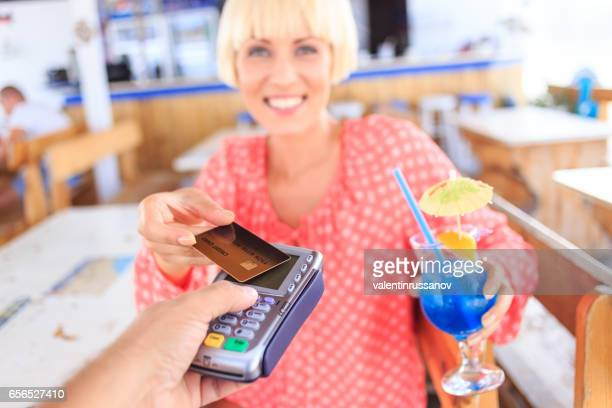 Young woman drinking cocktail and using credit card