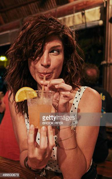 Young woman drinking cocktail at bar