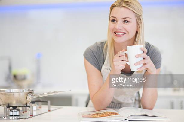 Young woman drinking coffee and looking at recipe book in kitchen