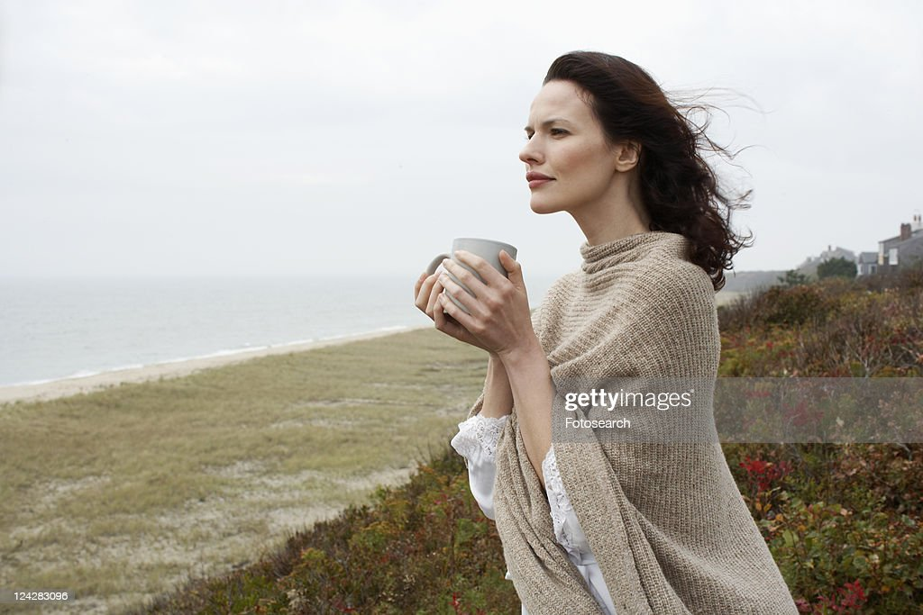Young woman drinking coffee at beach