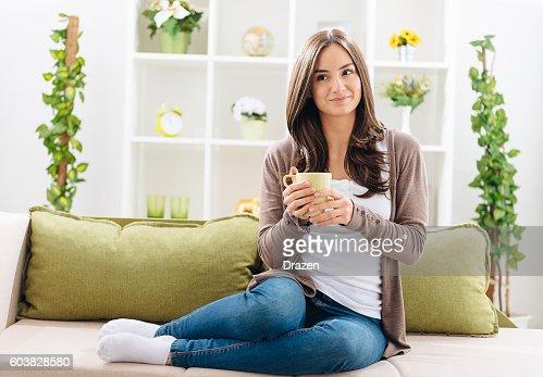 Junge Frau trinkt Kaffee wie zu Hause fühlen.
