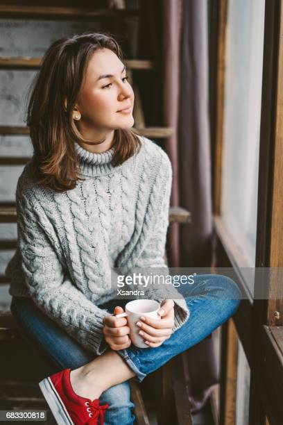 Young woman drinking coffee by the window