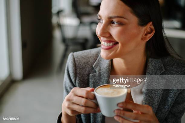 Young woman drinking coffee in cafe bar