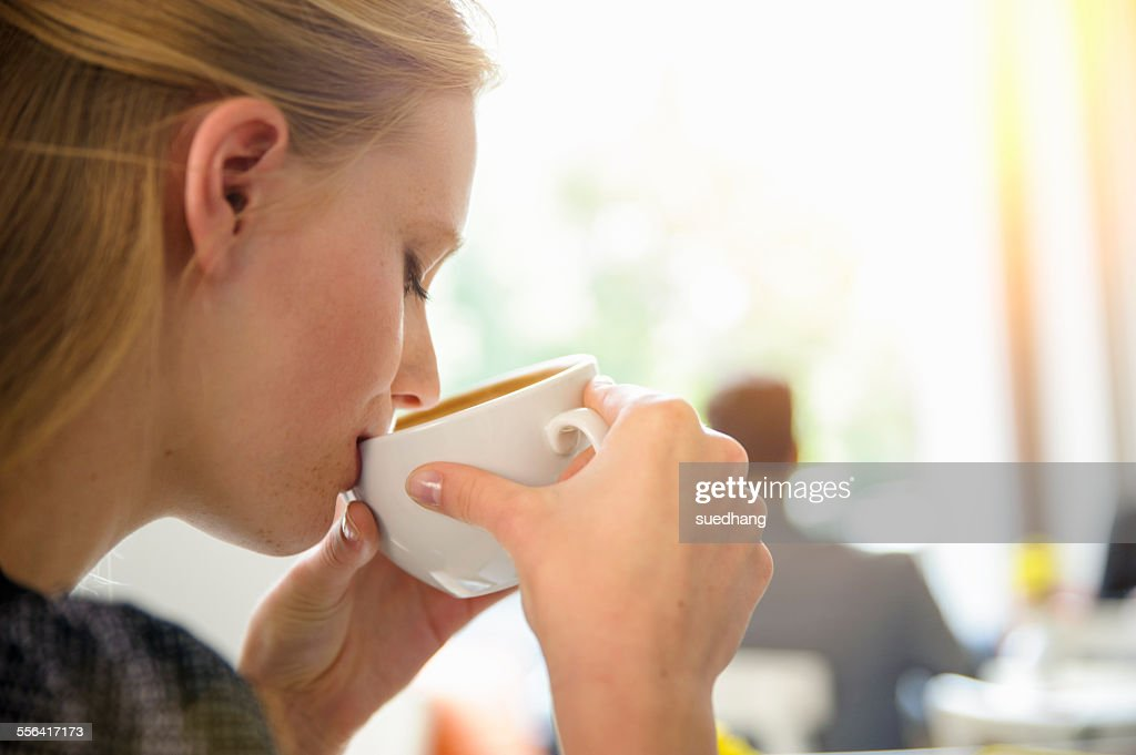 Young woman drinking coffee in cafe, close-up : Stock Photo