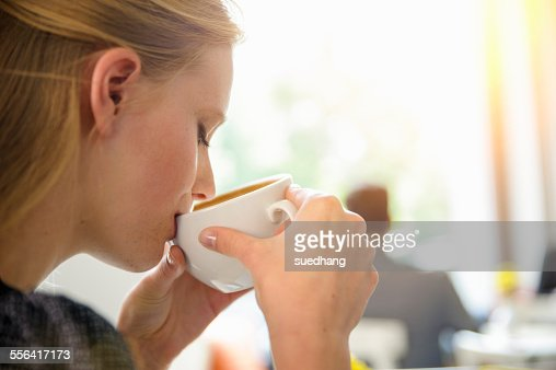 Young woman drinking coffee in cafe, close-up