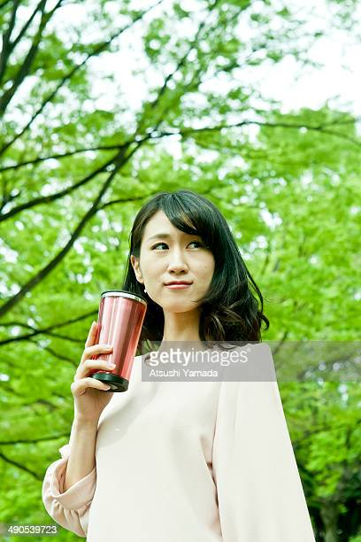 Young woman drinking coffee in park