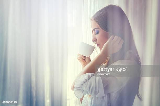 Giovane donna bere il caffè