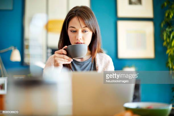 Young woman drinking coffee while using laptop at home