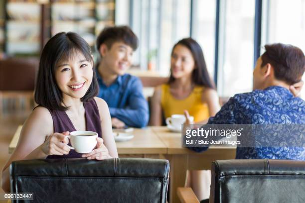 Young woman drinking coffee with friends in cafe