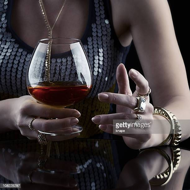 Young Woman Drinking Cognac and jewelry
