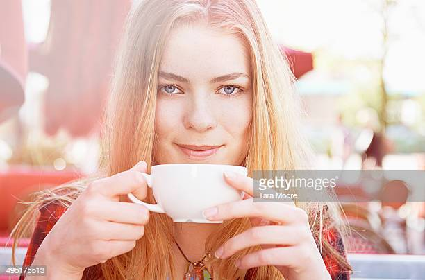 young woman drinking cup of coffee