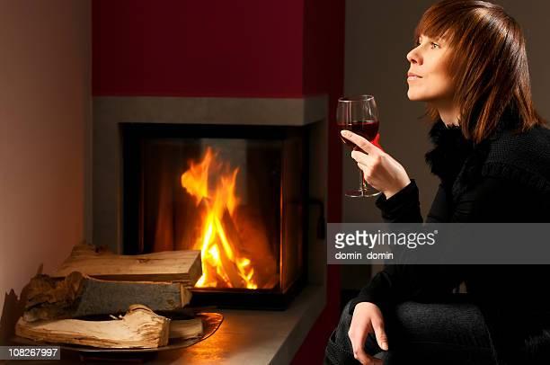 Jeune femme de boire, profitant de vin rouge, assis près de la cheminée