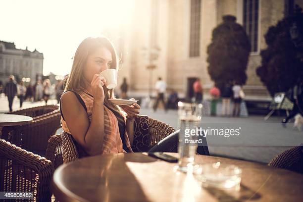 Jovem mulher beber café café em um café na cidade.