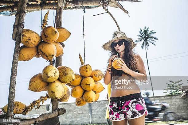 Young woman drinking from a coconut.