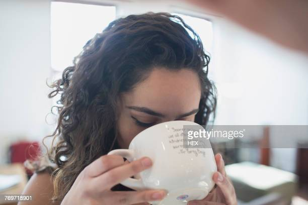 A young woman drinking from a mug
