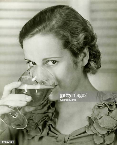 Young woman drinking glass of beer, (B&W), portrait