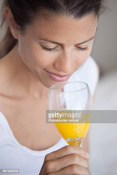 Young woman drinking glass of orange juice