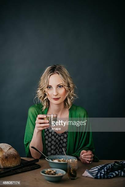 Joven mujer beber jugo o batido de verde