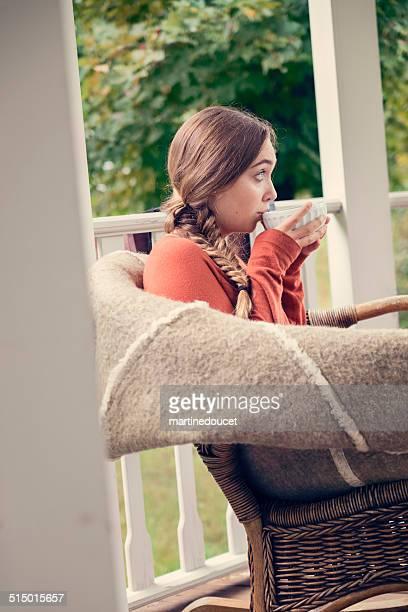 Junge Frau trinkt ein heißes Getränk an Land home porch.
