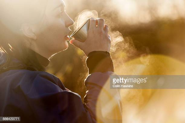 Young woman drinking hot drink in sunlight