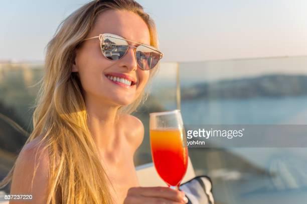 Jeune femme buvant à une terrasse de l'hôtel