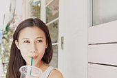 Young woman drinking juice, smiling