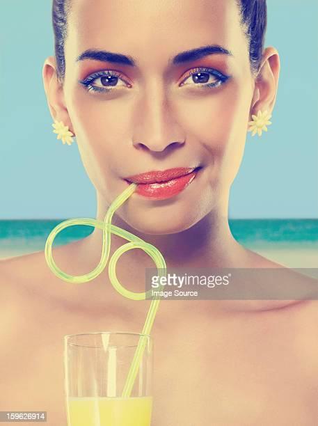 Giovane donna bere succo in paglia a ricciolo