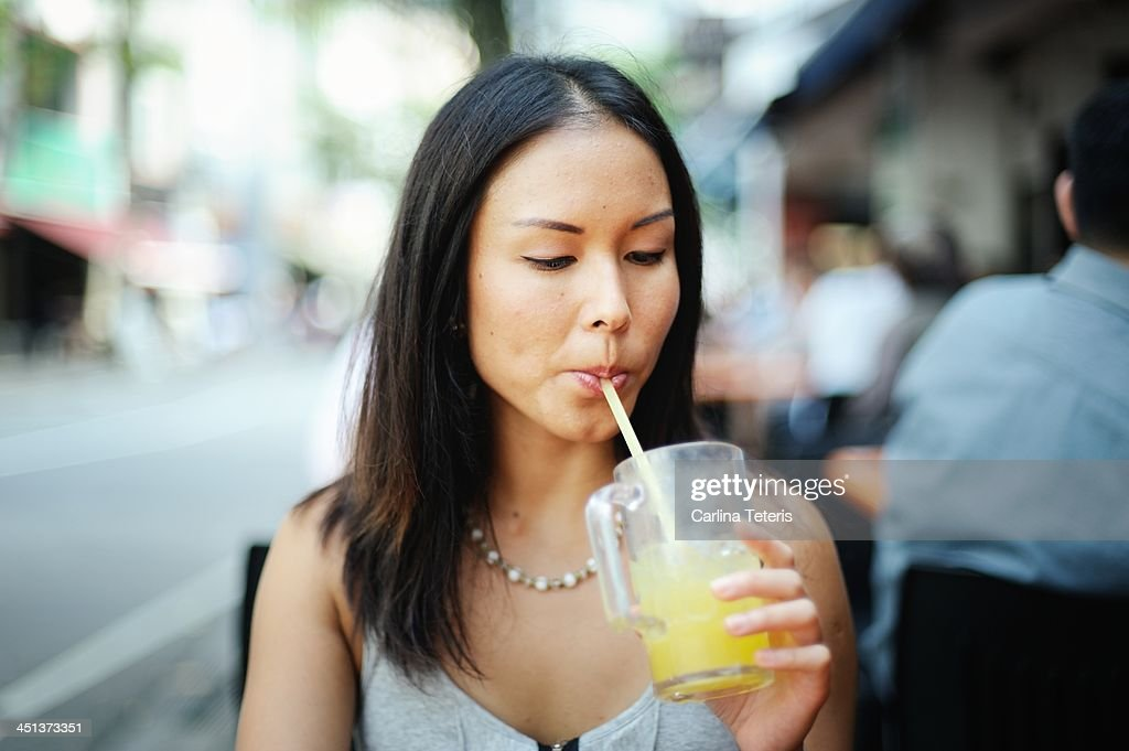 Young woman drinking lime juice : Stock Photo