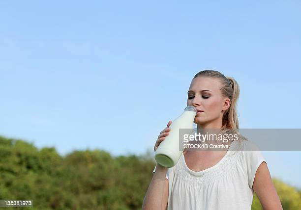 Young woman drinking milk from bottle outdoors