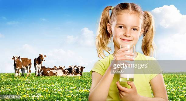 Young Woman Drinking Milk in Front of Field