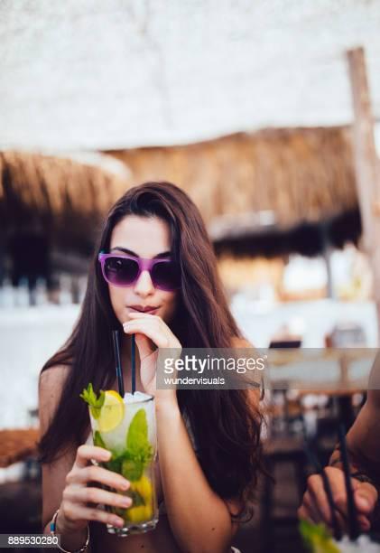 Young woman drinking mojito cocktail at summer tropical beach bar