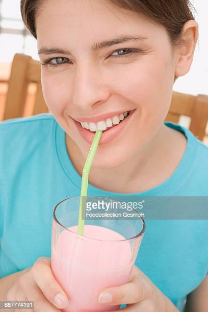 Young woman drinking strawberry milk through a straw