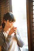 Young Woman Drinking Tea Beside the Window