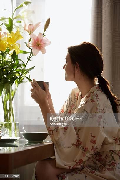 Jeune femme buvant du thé