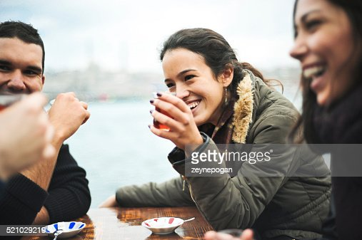 young woman drinking tea with a traditional turkish glass