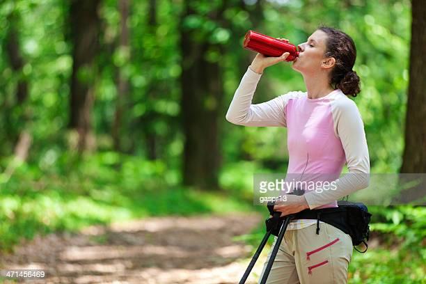 Junge Frau trinkt Wasser aus einer Flasche